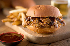 Pulled pork on a bun. A delicious pulled pork sandwich with barbecue sauce on a bun royalty free stock image