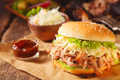 Pulled Pork Burger with Ketchup Sauce. Gourmet Pulled Pork Burger with Ketchup Sauce on Paper Above Wooden Table stock photography