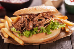 Pulled pork burger sandwich. American pulled pork burger sandwich with french fries Stock Photography