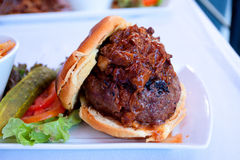 Pulled Pork Hamburger with Condiments on a Plate. Ground Sirloin Burger topped with pulled pork and garnished with pickle, tomato, lettuce plated on a white dish Royalty Free Stock Photos
