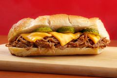 Pulled pork sandwich. Pulled pork baguette sandwich with cheese, cucumber and bbq sauce , red background Stock Photo