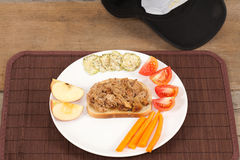 Pulled Pork Sandwich and Cap. An angled studio shot of a plated pulled pork open sandwich with garnishes of apple,tomatoes, carrots and dried cucumbers with a Stock Photography