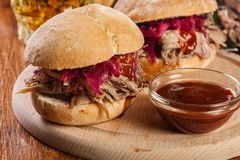 Pulled pork sandwich with red cabbage and bbq sauce. On cutting board royalty free stock photos