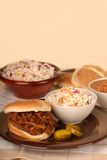 Pulled pork sandwich with slaw. A pulled pork sandwich with cole slaw, baked beans and pickles Stock Photos