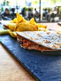 Pulled pork tacos sandwiches with fries on a black plate. People in background. royalty free stock photos