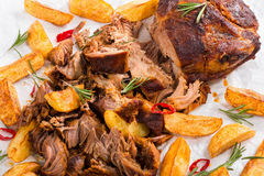 Pulled slow-cooked meat grilled in oven with fried potato wedges stock images
