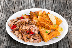 Pulled slow-cooked pork grilled in oven with fried potato stock images