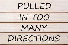 Pulled in Too Many Directions Concept of Stress. Pulled in Too Many Directions written on wood wall decor.Concept of stress, anxiety, pressure, confusion and Royalty Free Stock Photo