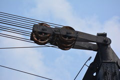 Pulley on crane. Pulley on large crane against blue skies on sunny day royalty free stock photography