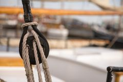 Pulley for sails and ropes made from wood on an old sail boat, with sail and other boats out of focus in the background. stock photo
