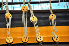 Pulleys of a boat. Blue sky and a view of a boat's pulleys with a rope running inside the circunference of an old yellow wooden ship stock photos