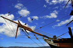 Pulleys of a boat. Blue sky and a view of the pulleys with a rope running inside the circunference of an old wooden ship royalty free stock photos