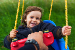 Pulling baby in swing Royalty Free Stock Photos