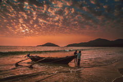 Pulling the boat to the beach. Local goa fisherman pulling the fishing boat back on the beach during stunning sunset, Goa Royalty Free Stock Photos