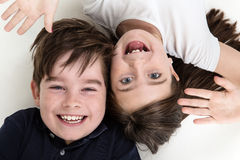 Pulling cheeky faces. Cheeky children pulling funny faces at each other whilst laying on the floor stock photos