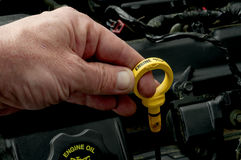 Pulling the dipstick to check oil level Stock Photography