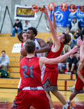 Pulling Down The Rebound. A Shasta player  (white) pulls down the rebound during a basketball game against  Foothill in Redding, California. December 5, 2015 Royalty Free Stock Photo