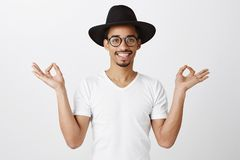 Pulling emotions together. Studio portrait of good-looking african man in trendy eyewear and black hat, raising hands. With zen gesture, smiling broadly Stock Photos