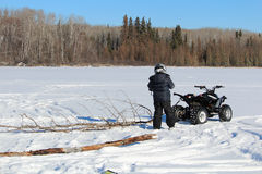 Pulling Firewood With a Quad to Make a Fire on the Ice Stock Image