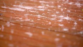 Rain on red deck outside. Pulling focus on rain falling on red deck outside on a sunny day stock footage