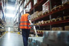 Pulling forklift. Worker in helmet and uniform pulling forklift with packed goods stock image