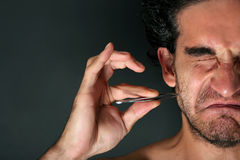 Pulling hair with tweezers Royalty Free Stock Photo
