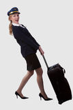 Pulling heavy luggage. Full body of a blond caucasian woman wearing flight attendent hat and suit pulling on a heavy suitcase over white stock photography