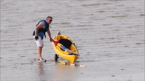 Pulling kayak on beach. Video footage of a man with kayak and equipment attaching wheels and pulling onto beach.videoed on whitstable beach 31st august 2016 stock footage
