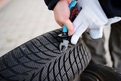 Pulling nail out of tire Stock Image