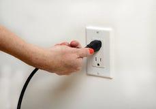 Pulling the plug. Woman with orange fingernails pulling the plug stock photos