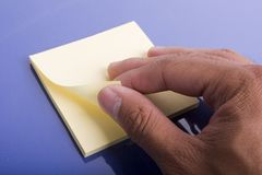 Pulling the post it Messages. Post peeling the post it pad Royalty Free Stock Photo