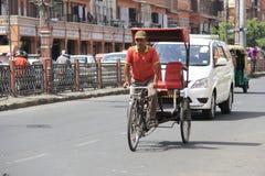 Pulling a Rickshaw in heat Stock Photo