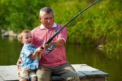 Pulling rod. Photo of grandfather and grandson pulling rod while fishing on weekend stock photography