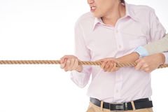 Pulling rope with anger. Cropped image of angry men pulling rope with his colleague Royalty Free Stock Photo
