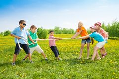Pulling the rope. Group of kids playing pulling the rope in the dandelion field Royalty Free Stock Images