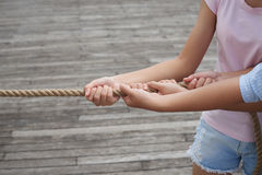 Pulling rope. Hands of girls pulling the rope: cooperation royalty free stock photo
