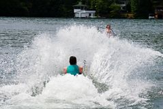 Pulling a Skier Out of the Water. Man on a slalom ski being pulled out of the water--he got up. Boat driver is barely visible behind the spray Royalty Free Stock Images