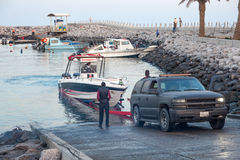 Pulling speed boat out of the water. KUWAIT - DEC 8: Young arab men pulling speed boat out of the water in Kuwait. December 8, 2014 in Al Kout, Kuwait, Middle Stock Image