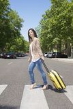 Pulling suitcase on crosswalk Stock Images