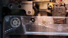 Pulling tape mechanism. Closeup of pulling tape mechanism inside vintage cassete player stock footage