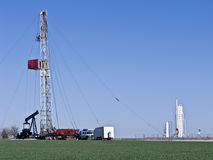 Pulling Unit-8547. Pulling unit servicing an oil well with men operating the unit.  One is high upon the derrick Stock Photos