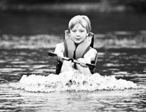 Pulling a Water Skier / Boy. Black and white shot of a young boy being pulled out of the water to ski royalty free stock photos