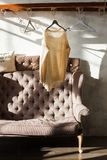 Pullover alla moda che appende sullo scaffale allo spogliatoio moderno con il sofà Ombre dure Immagini Stock