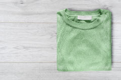 Pullover on wooden background. Green pullover folded on white wooden background Royalty Free Stock Photos