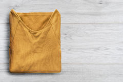 Pullover on wooden background. Yellow pullover folded on white wooden background Royalty Free Stock Photography