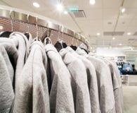 Pulls molletonnés ou hoodies gris dans le magasin d'achats, l'espace de copie Photographie stock