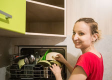 She pulls out the dishes from the dishwasher Royalty Free Stock Photo
