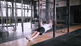 Pulls up on bar in gym. Efficient incline pull-ups to be fit. Best exercises in the gym. Strong man pulls up on bar in gym and wears lift and grip gear stock video footage