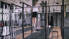 Pulls up on bar in gym. High pull-ups to chest to be fit. Best exercises in the gym. Strong middle-aged man pulls up on bar in gym and wears lift and grip gear stock video