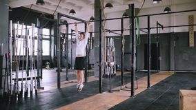 Pulls up on bar in gym. Pan view. High pull-ups to chest to be fit. Best exercises in the gym. Strong middle-aged man pulls up on bar in gym and wears lift and stock video footage